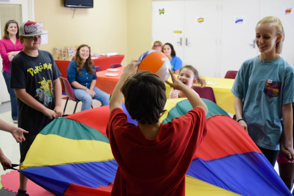 A boy throws a ball at the parachute that a group is playing with