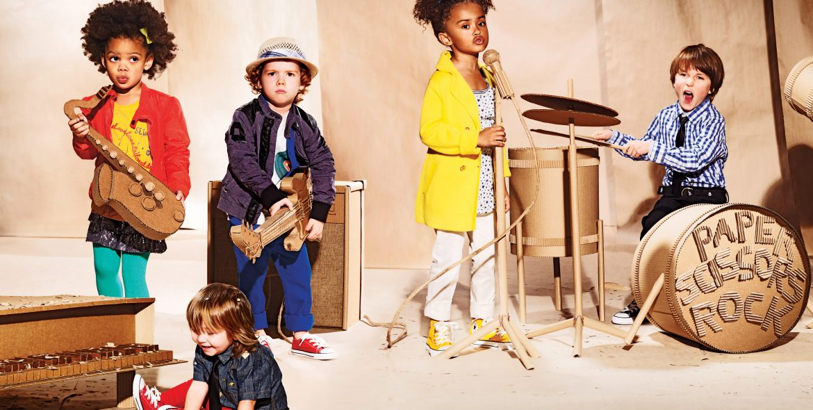 Five young children set up as if they were a rock band, playing various cardboard instruments including a piano, saxophone, guitar, drum set, and singing into a cardboard microphone