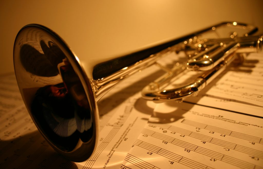 gold trumpet sitting on top of sheet music