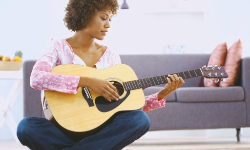 A women sitting on the floor in her living room playing the guitar, in blue jeans and a pink/white long sleeve blouse.