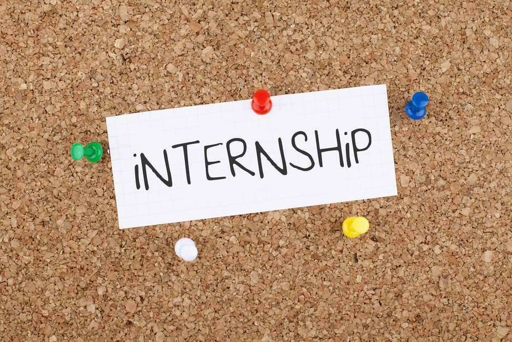 "A white piece of paper with the word ""internship"" written in a black marker on a pin board help up by push pins."