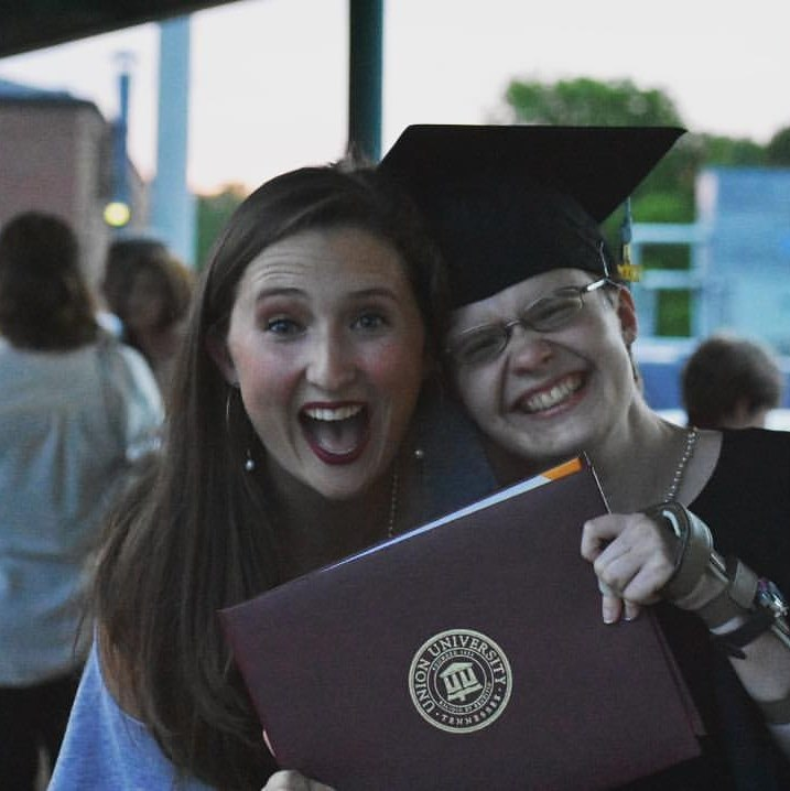 Two young girls holding college diploma