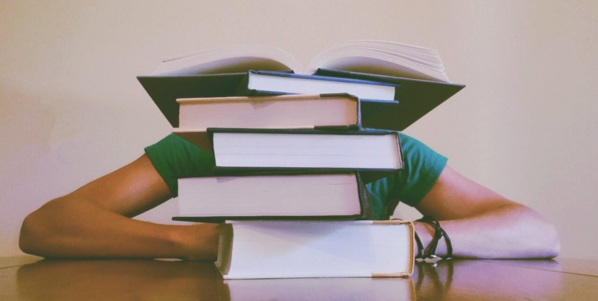 a student with books piled on head. what some might feel college success with ADHD feels like.